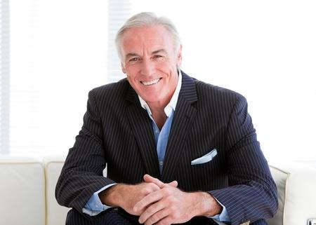 Happy senior businessman sitting on a sofa photo