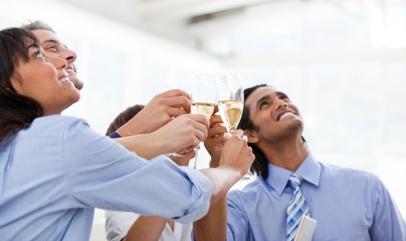 Cheerful multi-ethnic business team toasting with Champagne photo