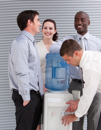 Smiling multi-ethnic business people interacting at a watercooler  Stock Photo - 10093402