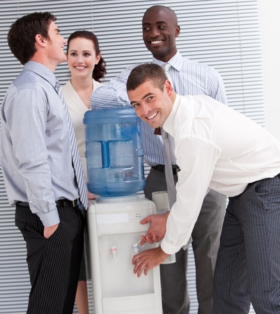 Confident multi-ethnic business people interacting at a watercooler photo