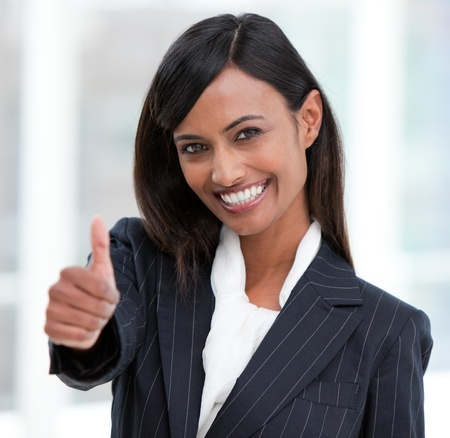 Cheerful businesswoman with a thumb up standing  Stock Photo - 10077947