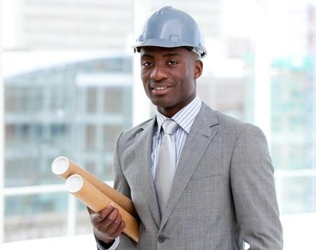 originator: Portrait of a charismatic male architect holding blueprints