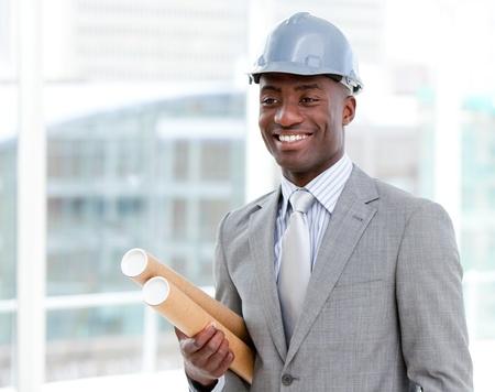 originator: Portrait of a cheerful male architect holding blueprints Stock Photo