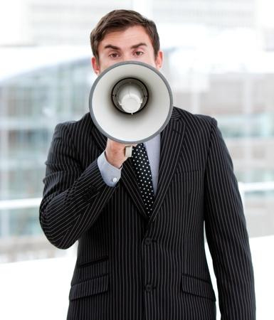 Stressed businessman yelling through a megaphone  photo