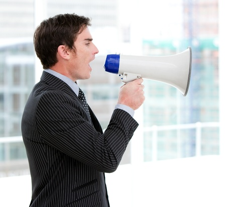 Frustrated businessman yelling through a megaphone  photo