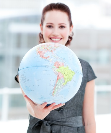 Assertive businesswoman holding a terrestrial globe photo