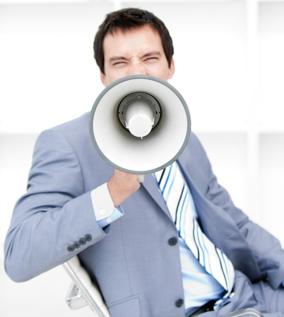 Furious young businessman yelling through a megaphone photo