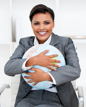 Charismatic businesswoman holding a terrestrial globe photo