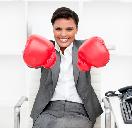 Attractive businesswoman wearing boxing gloves sitting at her desk Stock Photo - 10076238