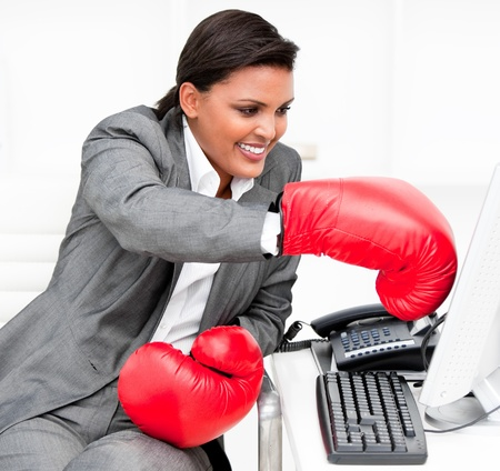 Young businesswoman wearing boxing gloves punching a computer Stock Photo - 10076626
