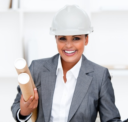 Positive female architect holding blueprints photo