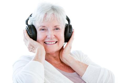 Smiling senior woman listening music with headphones photo