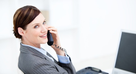 Smiling businesswoman on phone sitting at her desk photo