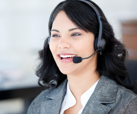 Joyful businesswoman wearing a headset to talk with customer photo