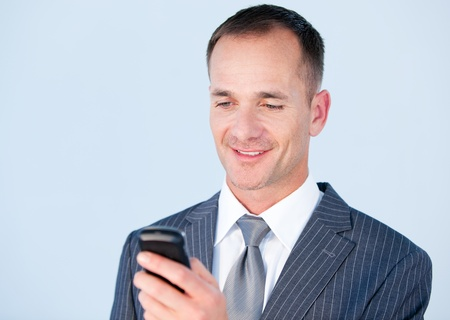 Handsome businessman sending a text with his  phone  photo