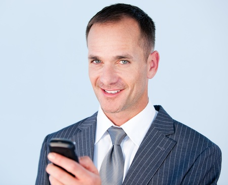Confident businessman sending a text with his  phone  photo