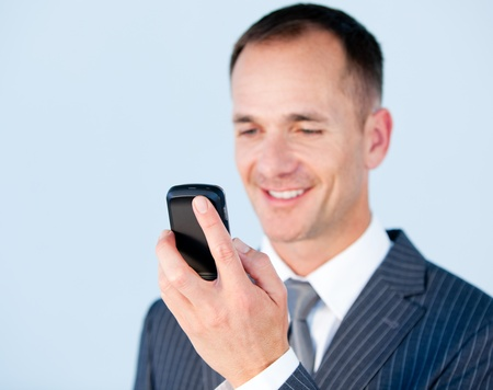 Self-assured businessman sending a text with his  phone photo