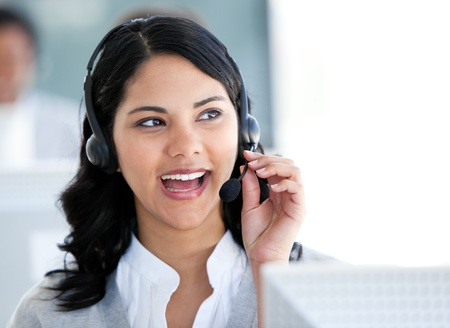 Beautiful businesswoman talking with clients in front of her computer  photo