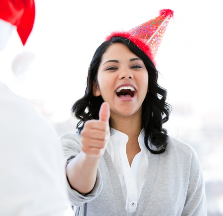 thumbup: Positive businesswoman doing a thumb-up to celebrate christmas Stock Photo