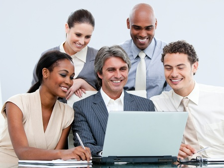 teaming: Happy mixed businessteam looking at the laptop