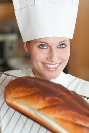Cheerful female chef baking bread  photo
