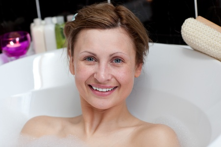 Jolly young woman having a bath  photo