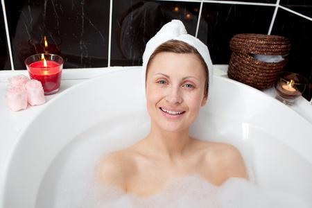 bathtowel: Positive woman relaxing in a bubble bath