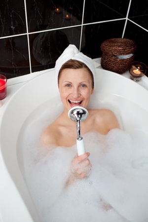 Happy woman singing in a bubble bath  photo