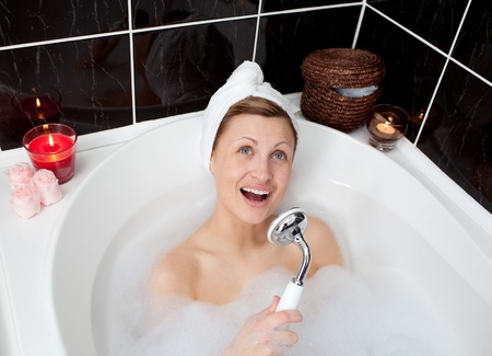 bathtowel: Cheerful young woman singing in a bubble bath Stock Photo