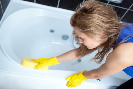 Young woman cleaning a bath photo