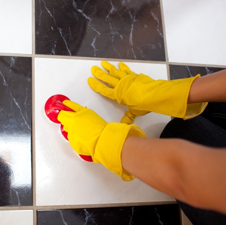 Close-up of a woman cleaning a bathrooms floor  photo