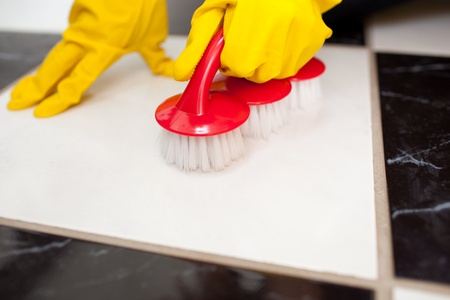 A person cleaning a bathrooms floor with a yellow rubber glove photo