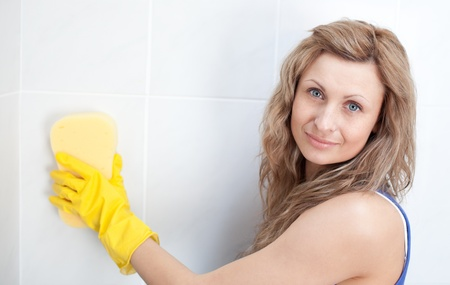 Young woman cleaning a bathroom photo