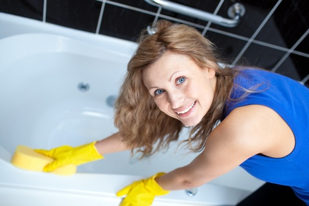 Smiling woman cleaning a bath photo