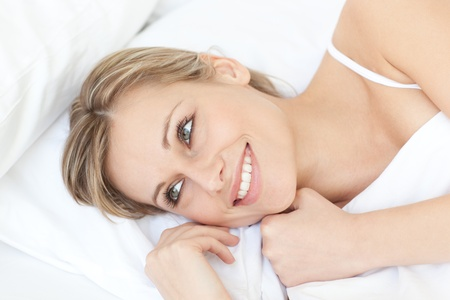 Radiant relaxed woman lying on her bed  photo