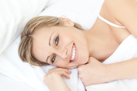 Bright relaxed woman lying on her bed photo