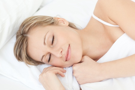 sleeping woman: Bright tired woman sleeping on her bed  Stock Photo