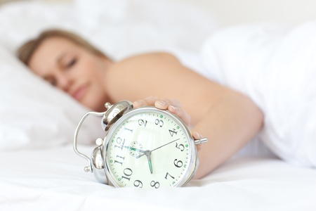 Young woman holding an alarm clock photo