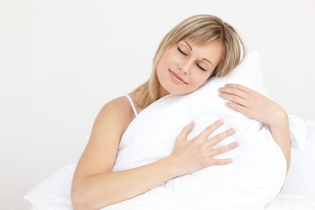 Relaxed woman hugging her cushion sitting on her bed photo