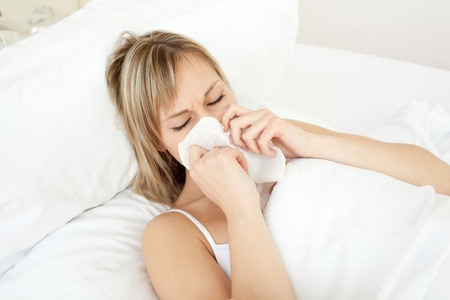 Sick woman blowing lying on her bed photo