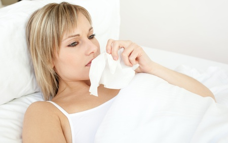 Upset sick woman blowing lying on her bed
