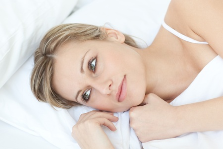 Beautiful relaxed woman lying on her bed photo