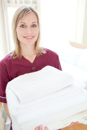 hotel worker: Positive cleaning lady holding towels