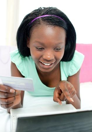 Cheerful teen girl shopping on-line Stock Photo - 10094860