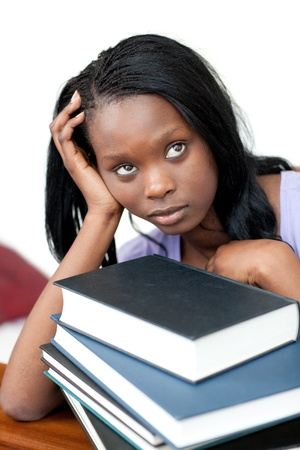 Upset student leaning on a stack of books photo