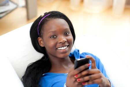Bright woman sending a text lying on a sofa photo