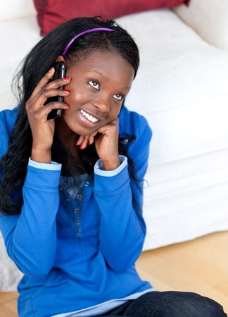 Pretty young woman talking on phone sitting on the floor Stock Photo - 10094134