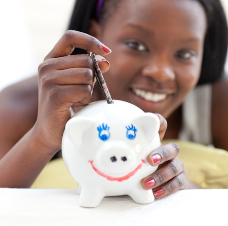 Smiling teen girl putting money in a piggy-bank  photo