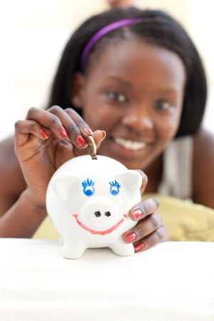 Happy teen girl putting money in a piggy-bank photo
