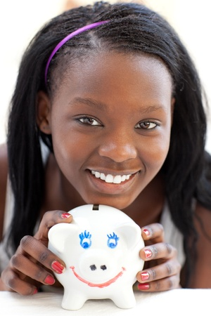 Bright teen girl holding a piggy-bank Stock Photo - 10094861